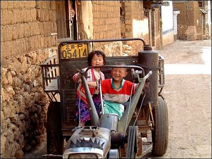 China, Yunnan - Baisha, kids playing on a tractor