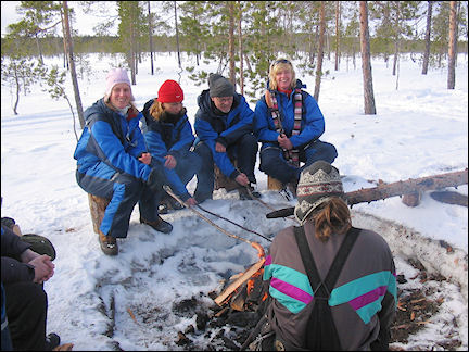 Finland, Lapland - Heating sausages over a campfire
