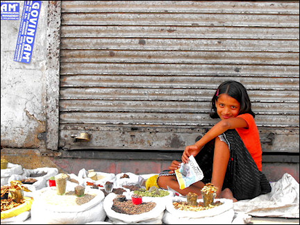 India, Delhi - A young girl selling local spices in the street