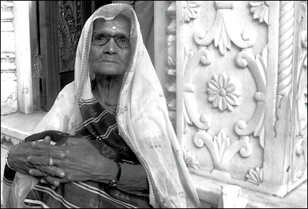 India, Delhi - An old lady sitting on the temple porch gives her blessings to visitors