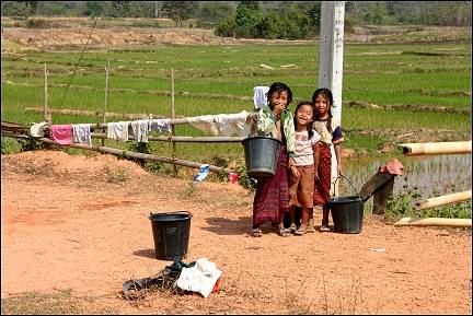 Laos - Thalat, girls doing laundry in an irrigation canal