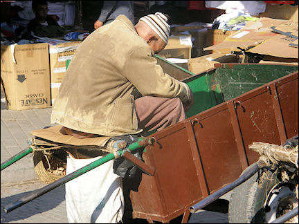 Morocco, Marrakech - Man waiting for customers on top of his hand cart