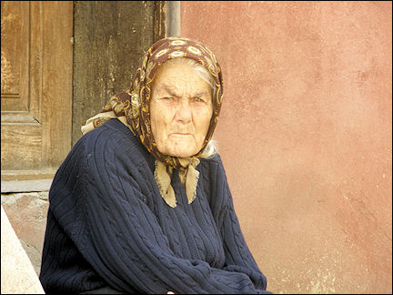 Romania - Old people with weather-beaten faces sit on benches in front of their houses