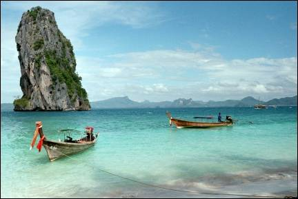 Thailand - Blue sea with limestone rock and fishing boats