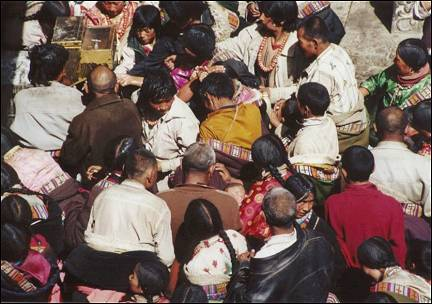 Tibet - Pilgrims pushing and shoving around a water pump